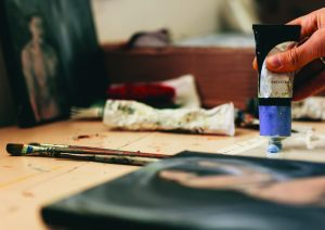 Close up of female artist hands with colors. Cropped shot of woman getting paint from tube in her studio.